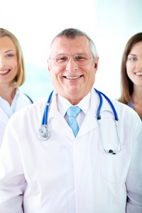 Portrait of happy senior therapeutist looking at camera with his assistants behind