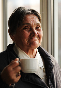 Portrait of Happy Smiling Senior Woman Beside the Window and Drinking Coffee, looking at camera