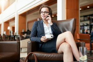 Portrait of happy young businesswoman sitting in cafe talking on mobile phone. Female executive with cup of coffee using cell phone and looking away.