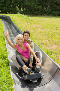 Portrait of happy young couple enjoying summer sledge ride