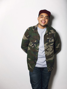 Portrait of happy young guy wearing camouflage jacket. Hispanic male model posing against white background