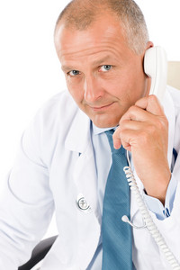Portrait of hospital professional doctor with stethoscope on phone isolated
