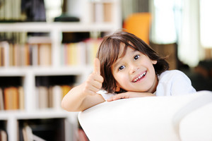 Portrait of little boy sitting on couch looking at camera and smiling