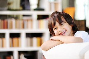 Portrait of little boy wearing white t-shirt, sitting at couch looking at camera smiling