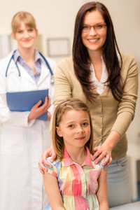 Portrait of little girl with mother and pediatrician in background