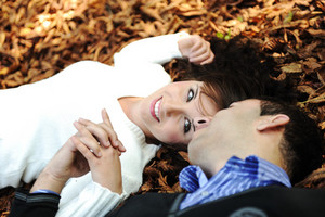 Portrait of love couple laying down outdoor in park looking happy on fall ground