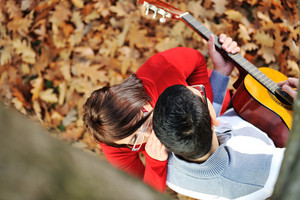 Portrait of love couple playing guitar in park