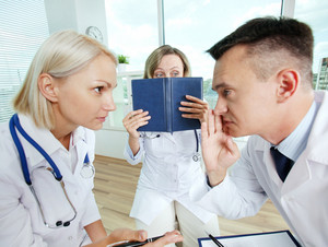 Portrait of male clinician and his colleague conspiring with scared co-worker near by