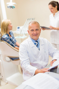 Portrait of mature dentist surgeon at dental office with patient