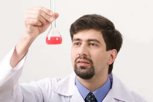 Portrait of medical specialist looking at flask on a white background
