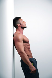 Portrait of muscular man leaning against the wall and looking up