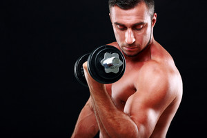 Portrait of muscular man lifting dumbbell on black background