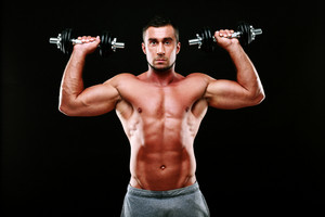 Portrait of muscular man lifting dumbbells over black background