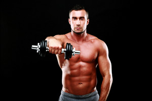 Portrait of muscular man working out with dumbbell over black background