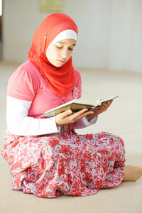 Portrait of muslim girl reading Islamic holy book of Koran