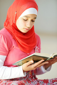 Portrait of muslim girl reading Islamic holy book of Koran