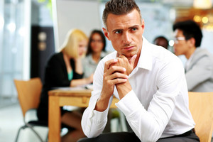 Portrait of pensive businessman sitting in front of colleagues