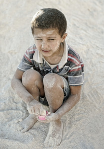 Portrait of poverty, little poor dirty boy in sand