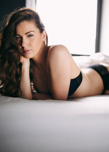 Portrait of pretty woman wearing black lingerie lying on bed. Sexy female model on bed looking at camera.