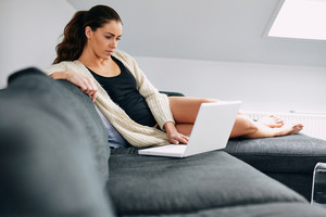 Portrait of pretty young lady sitting on couch surfing internet on laptop. Relaxed female model using laptop at home.