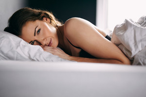 Portrait of pretty young woman lying in her bed looking at camera with a smile.