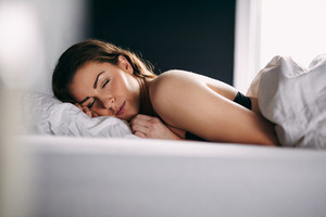 Portrait of relaxed young lady sleeping in her bed. Female model sleeping peacefully in her bed.