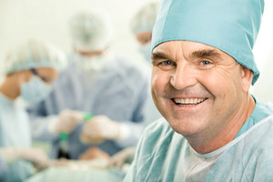 Portrait of senior doctor smiling on the background of his colleagues