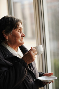 Portrait of Senior Woman Looking Through Window and Drinking a Cup of Coffee