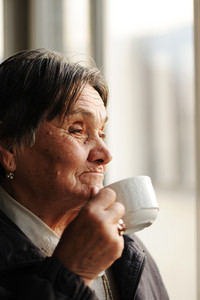 Portrait of Senior Woman Looking Through Window and Drinking Coffee