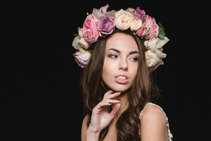 Portrait of sensual seductive young female in flower wreath isolated over black background