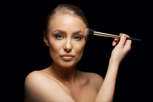Portrait of sensual young lady applying foundation on her face with a make up brush. Pretty young female fashion model against black background.