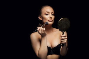 Portrait of sensual young lady wearing black bra applying foundation on her face with a make up brush. beautiful young female fashion model with mirror against black background.