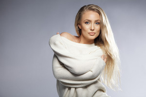 Portrait of sensual young woman wearing oversized sweater looking at camera. Beautiful caucasian female fashion model posing on grey background with copyspace.