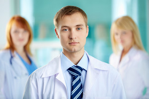 Portrait of serious clinician in white coat looking at camera