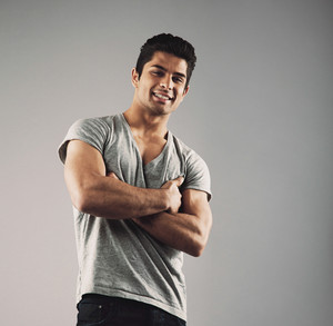 Portrait of smart young muscular man posing against grey background. Happy young hispanic male model standing with his arms crossed looking at camera smiling.