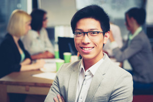 Portrait of smiling asian businessman sitting in front of colleagues