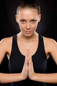 Portrait of smiling young woman performing yoga with hands clasped