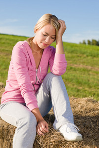 Portrait of sportive young woman relax sitting on hay bales