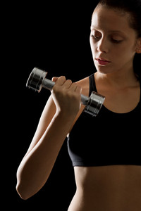 Portrait of sporty young woman holding dumbbell on black background