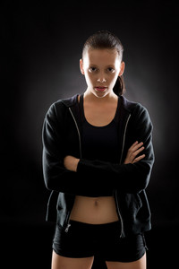 Portrait of sporty young woman on black background