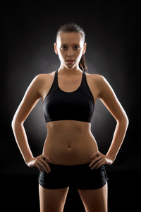 Portrait of sporty young woman standing akimbo on black background