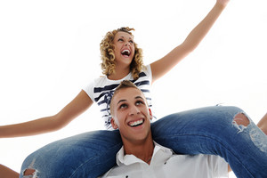 Portrait of teenage couple piggybacking isolated in white