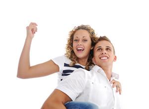 Portrait of teenage couple piggybacking isolated in white