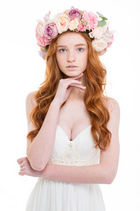 Portrait of tender charming young woman with wavy red hair in wedding dress and wreath of pink roses over white background