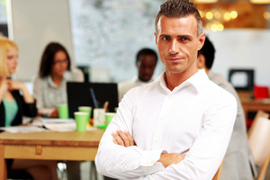 Portrait of thoughtful businessman with arms folded sitting in front of colleagues
