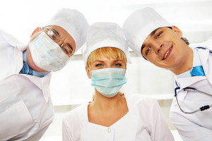 Portrait of three therapeutists in masks looking at camera