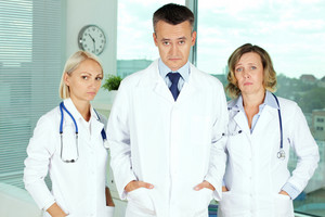 Portrait of three uniformed doctors not being optimistic about the healthcare system