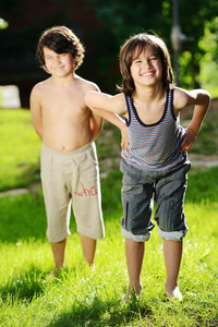 Portrait of two little kids outdoor in a summer meadow standing together