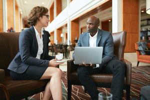 Portrait of two young business colleagues sitting at coffee shop. African businessman with laptop and businesswoman with cup of coffee discussing work.