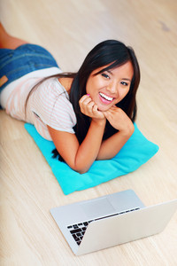 Portrait of young beautiful asian woman lying on the floor with laptop at home